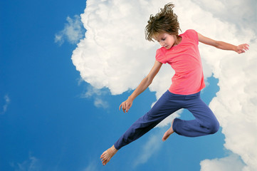 cute young dancer girl jumping against bue sky