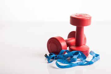 Red dumbbells weight with measuring tape