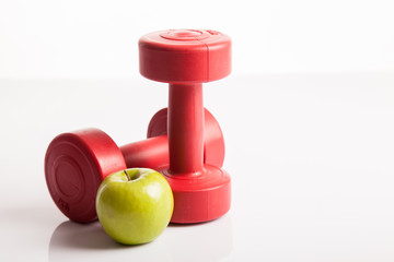 Red dumbbells weight with green apple
