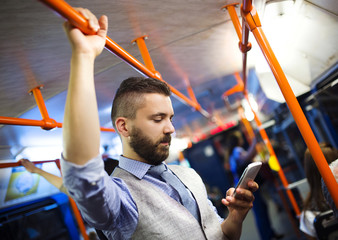 Hipster businessman with mobile phone on tram