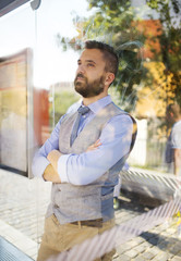 Hipster business man waiting for bus