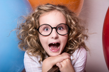 Happy surprised girl in glasses with an open mouth