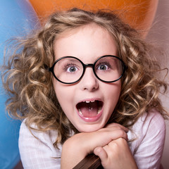Happy surprised girl in glasses with an open mouth.