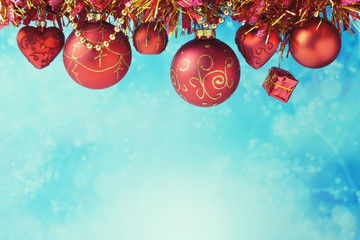 Christmas ornaments hanging over blue bokeh background