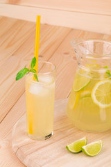 Pitcher full of lemonade on wooden table.