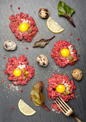 Beef tartare with egg, capers and onions on dark background