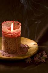 Brennende Kerze und rauchende Räucherstäbchen