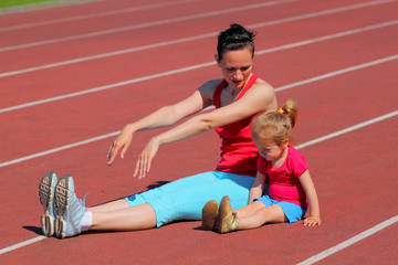 Mother and little daughter are running in the stadium.