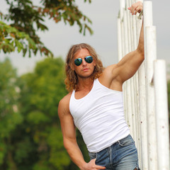 sexy caucasian fit man in sunglasses posing near