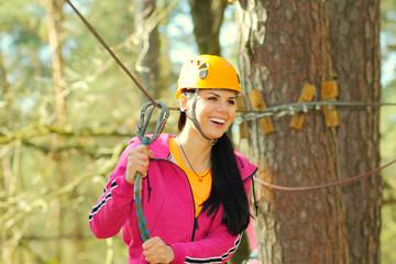 positive cheerful girl having fun doing tree climbing.