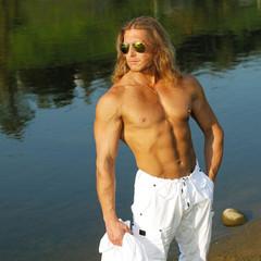 Handsome fitness model man walks along the beach