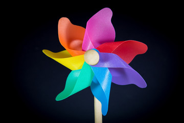a beautiful colored pinwheel spinning faster in the wind