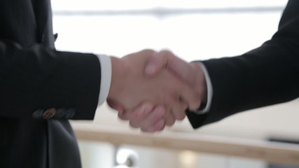 A handshake of two businessmen in the suits