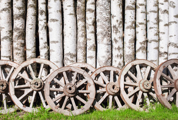 Old wooden birch fence with wooden wheels