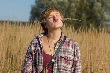 Девушка делает смешное лицо в поле с колосками