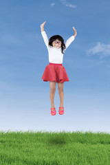 Cheerful little girl jumping on meadow