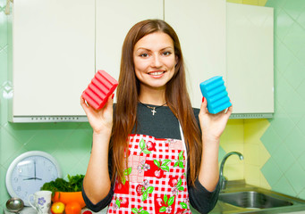 housewife shows two sponges of different colors