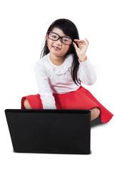 Cute little girl using laptop computer
