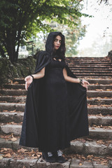 beautiful dark vampire woman with black mantle and hood