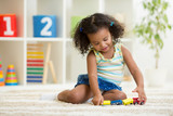 Kid girl playing toys at kindergarten room