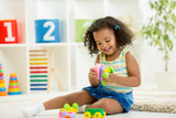 Kid girl playing toys at kindergarten room poster