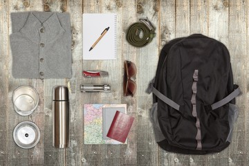 Several hiking items, on top of rustic wooden table.