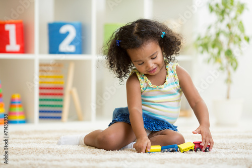 canvas print picture Kid girl playing toys at kindergarten room