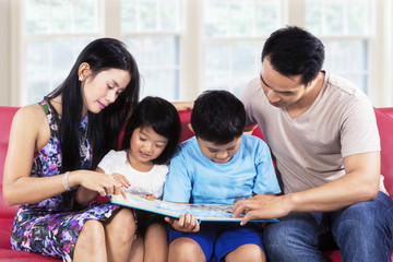 Happy family read story book on sofa