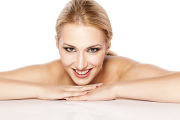 beautiful smiling blonde with makeup lying on white