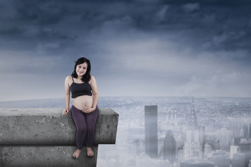 Pregnant mother sitting on rooftop