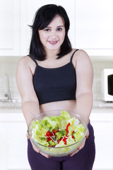 Pregnant woman showing salad