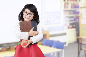 School girl holds book and apple in class
