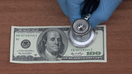 economist with stethoscope looking dollar banknote health