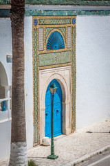 A blue door with black studs and stone ornament at doorway in Tu
