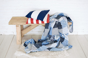 Patchwork quilt on rustic bench