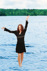 Pretty woman walking on water, at outdoor lake
