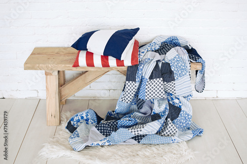 Patchwork quilt on rustic bench - 71439779