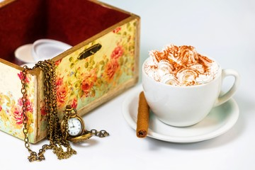 Cup of coffee with cream, next to jewelry box.