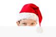 Young boy in red Santa hat hiding behind a blank paper