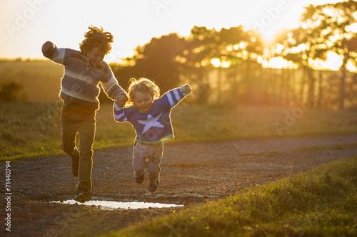Leinwanddruck Bild two boys jumping over puddles