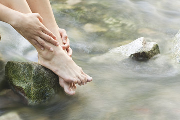 Womans feet in a forest creek