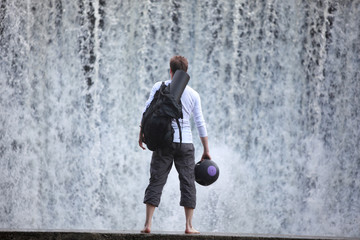 Fit man  on footbridge at the waterfall watching water
