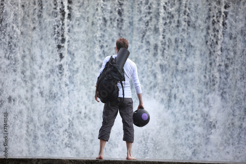 canvas print picture Fit man  on footbridge at the waterfall watching water