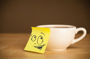 Post-it note with smiley face sticked on cup