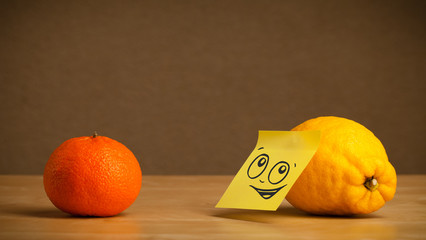 Lemon with post-it note looking at orange