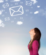 Young girl looking at mail symbol clouds on blue sky