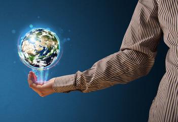 Businessman holding a glowing earth globe