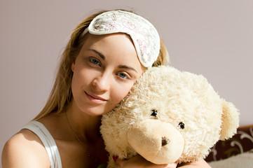 young woman with sleep bandage hugging teddy bear