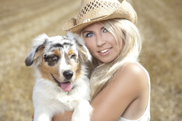 Beautiful, blonde young woman with cowboy hat and cute dog
