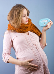 Young pregnant woman measures the temperature in the room